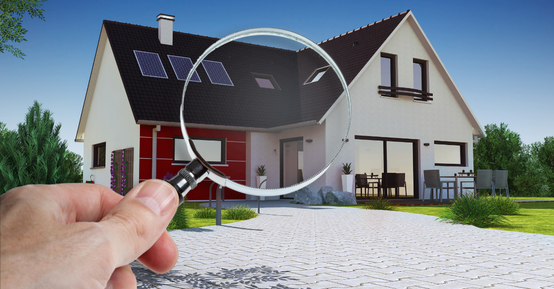A man holds a magnifying glass up to a home, representing a pre-offer home inspection.