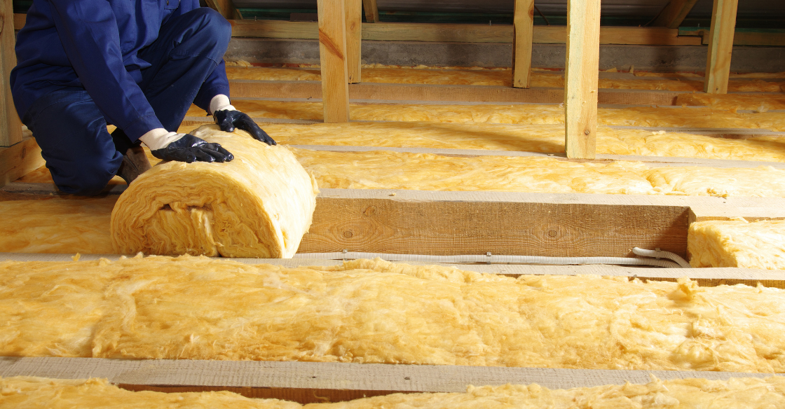 A man installs insulation in an attic for energy efficiency.